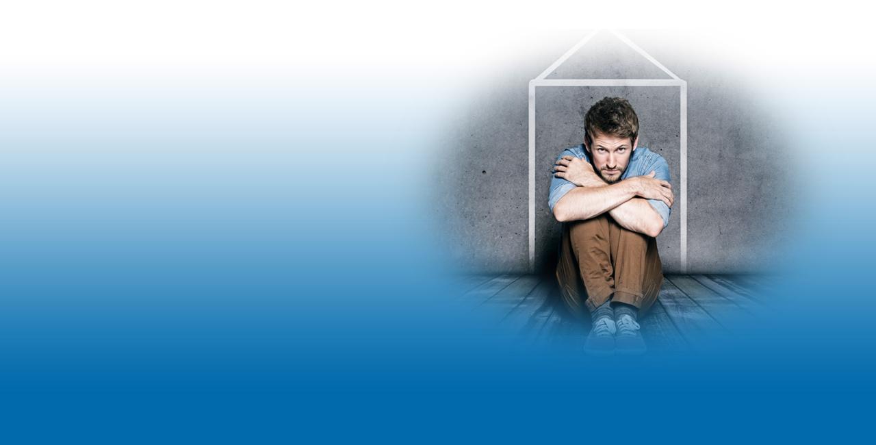 Junger Mann sitzt niedergeschlagen in der Ecke