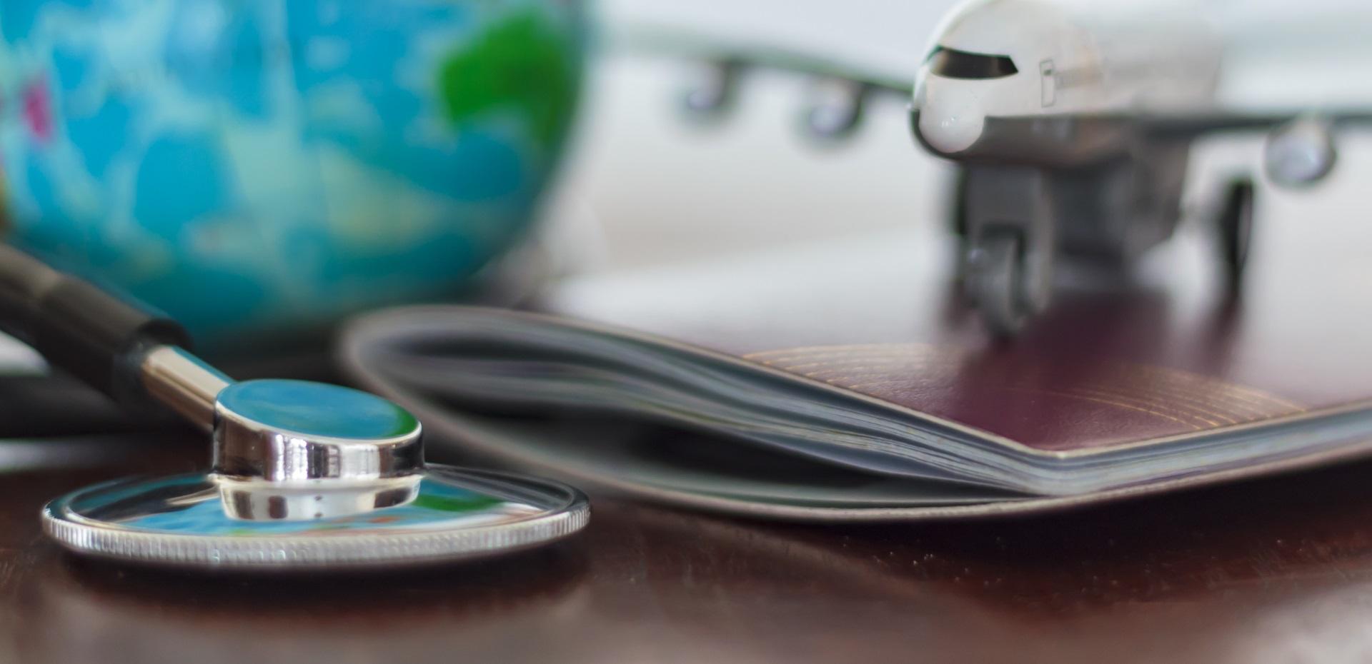 Ein Globus, ein Modellflugzeug, ein Impfpass und ein Stethoskop