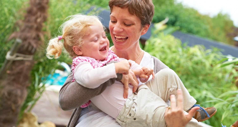 Mutter hält ihre lachende Tochter auf dem Arm
