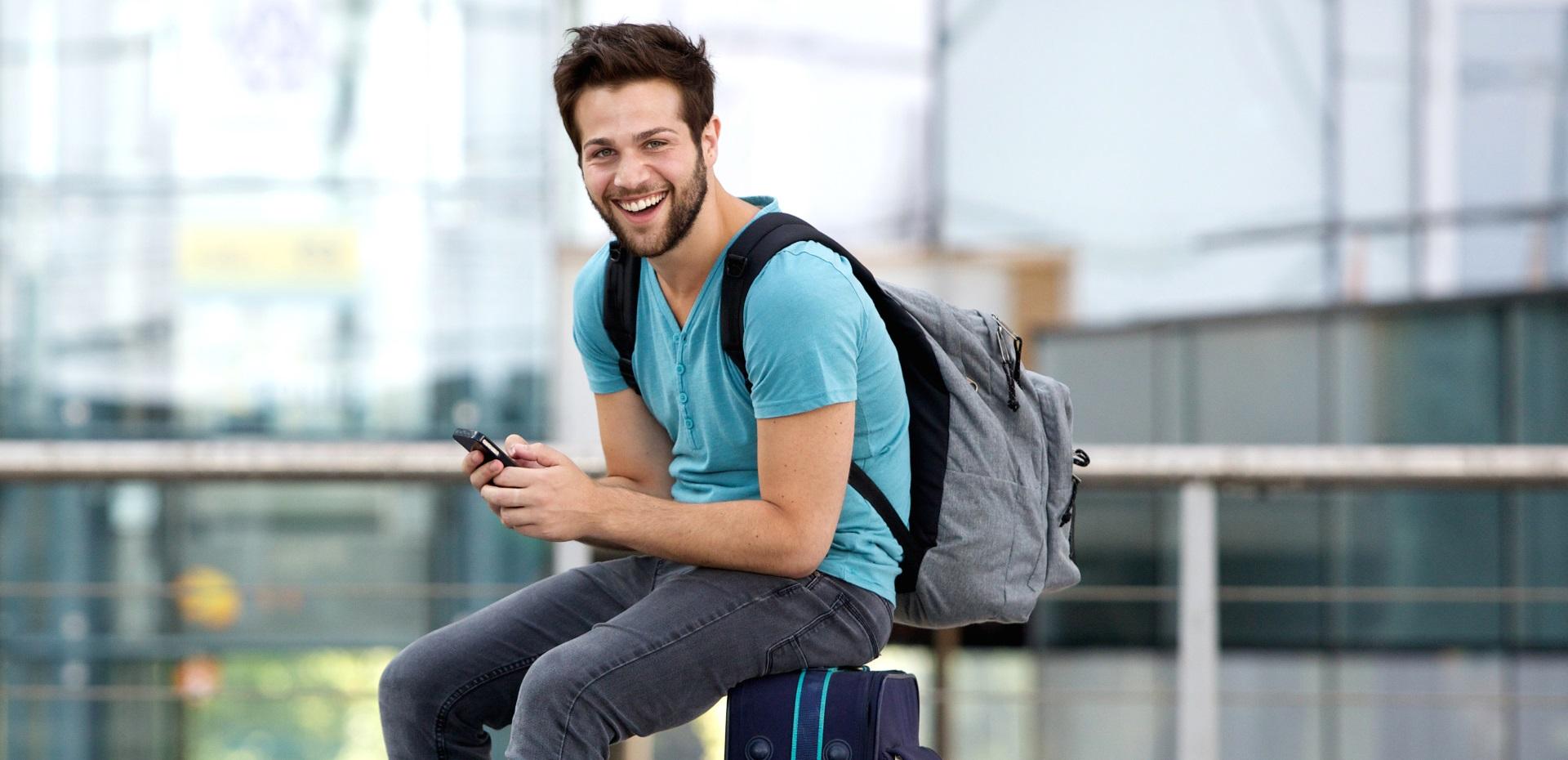 Junger Mann sitzt reisebereit auf einem Koffer