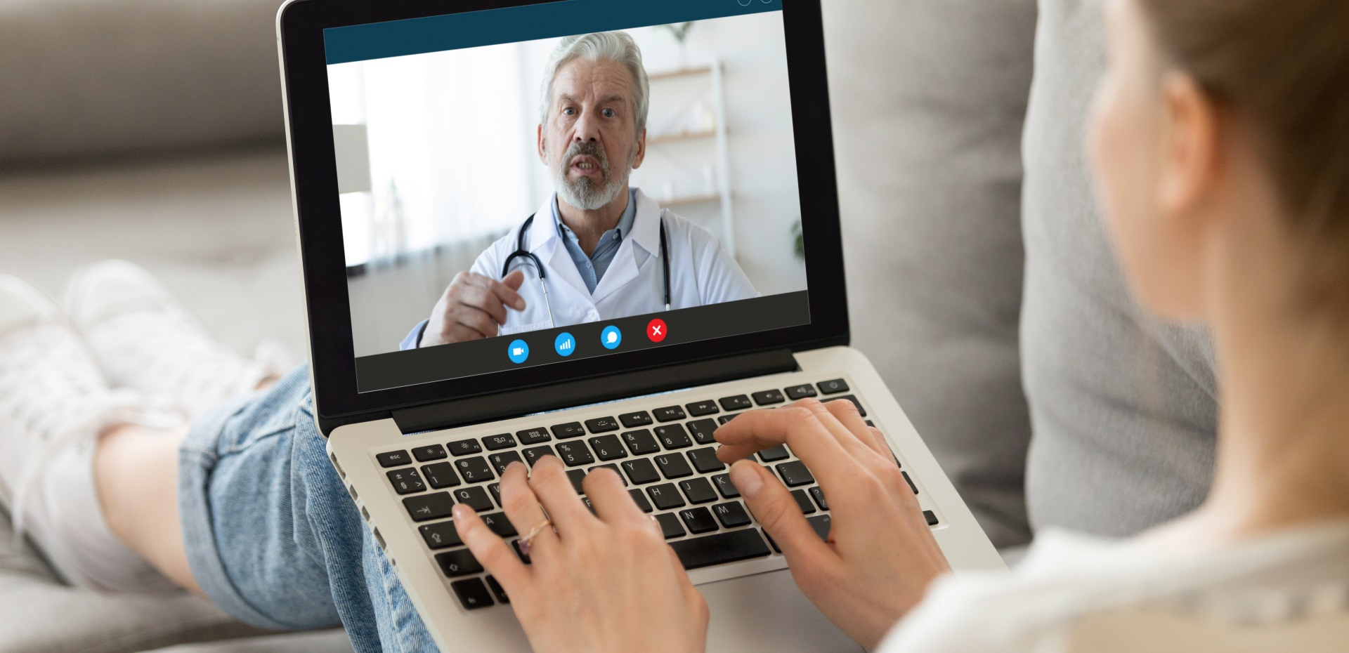 Frau sitzt auf dem Sofa und ist über einen Laptop mit Arzt in Videosprechstunde