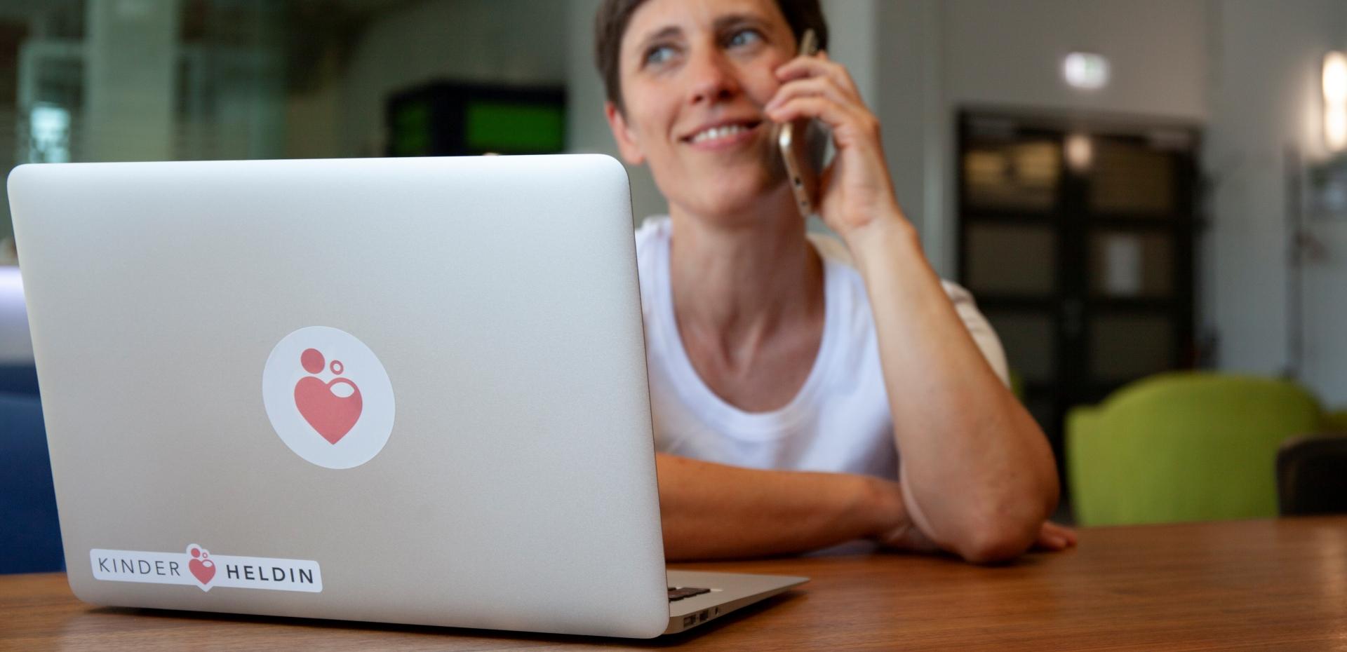 Eine Hebamme von Kinderheldin sitzt vor einem Laptop und telefoniert