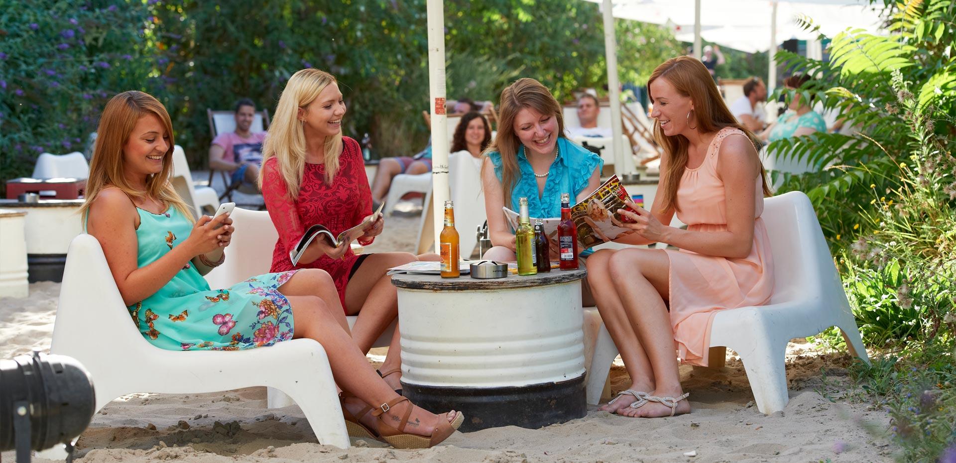 Vier junge Frauen in einer Beachbar beim Lesen, Reden und Lachen