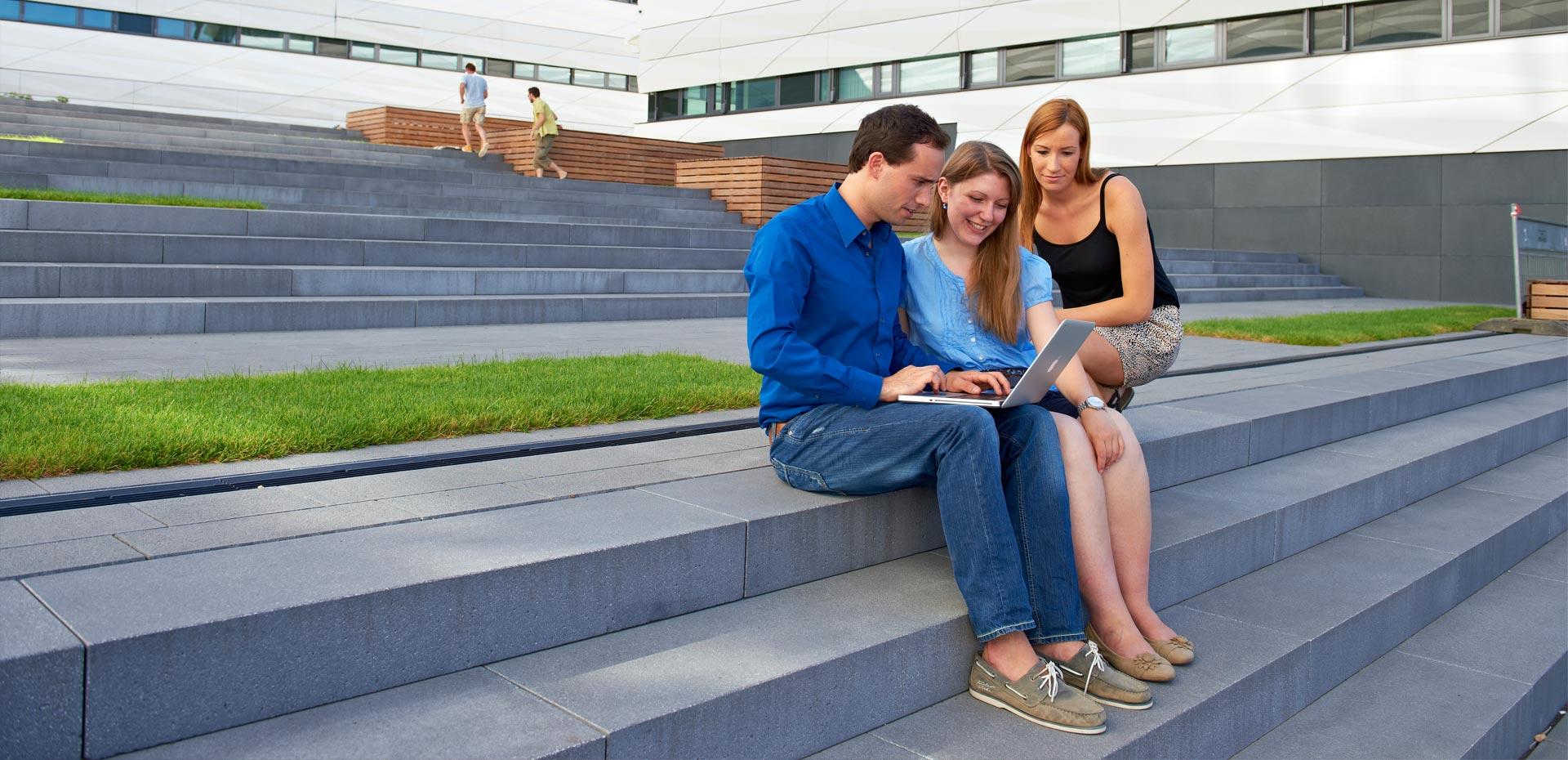 Drei junge Leute mit einem Laptop auf einer Treppe vor Bürogebäuden