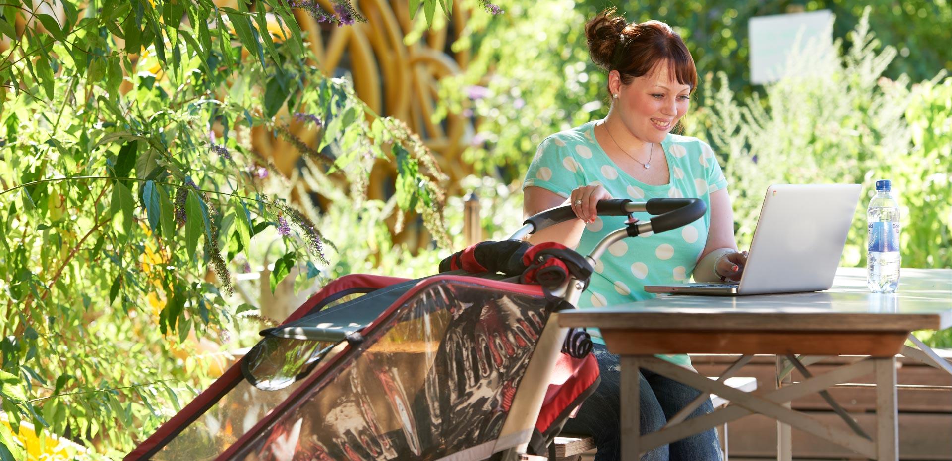Junge Frau mit Kinderwagen und einem Laptop
