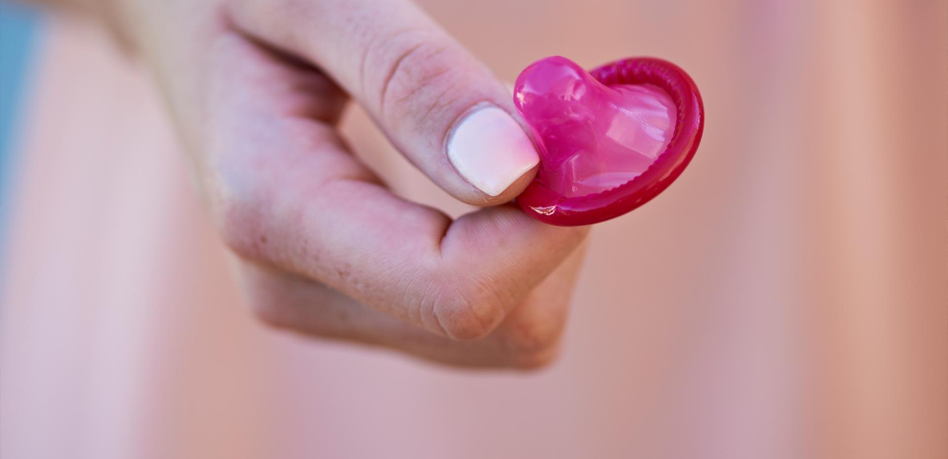 Frauenhand mit rosa Kondom