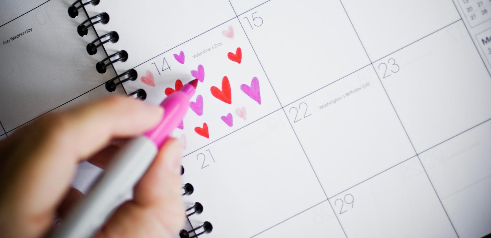 Kalender mit Eintrag von roten und rosa Herzchen