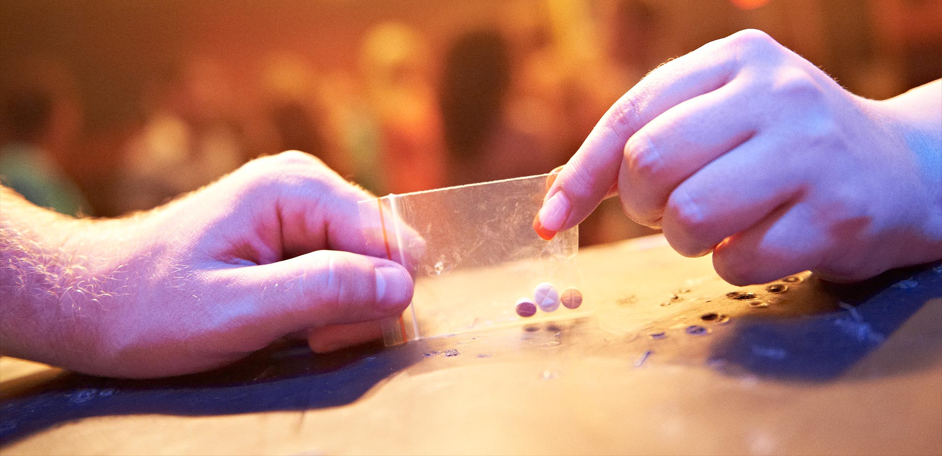 Hände in Großaufnahme, die Pillen in Beutel übergeben