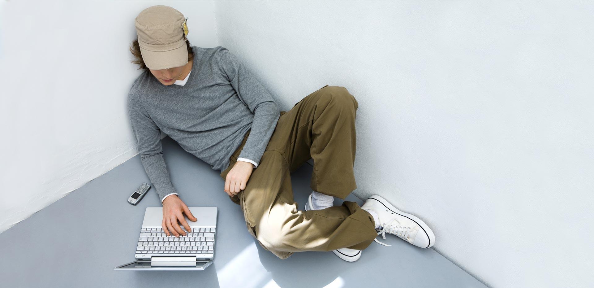 Junger Mann mit Computer halb liegend in einer Zimmerecke