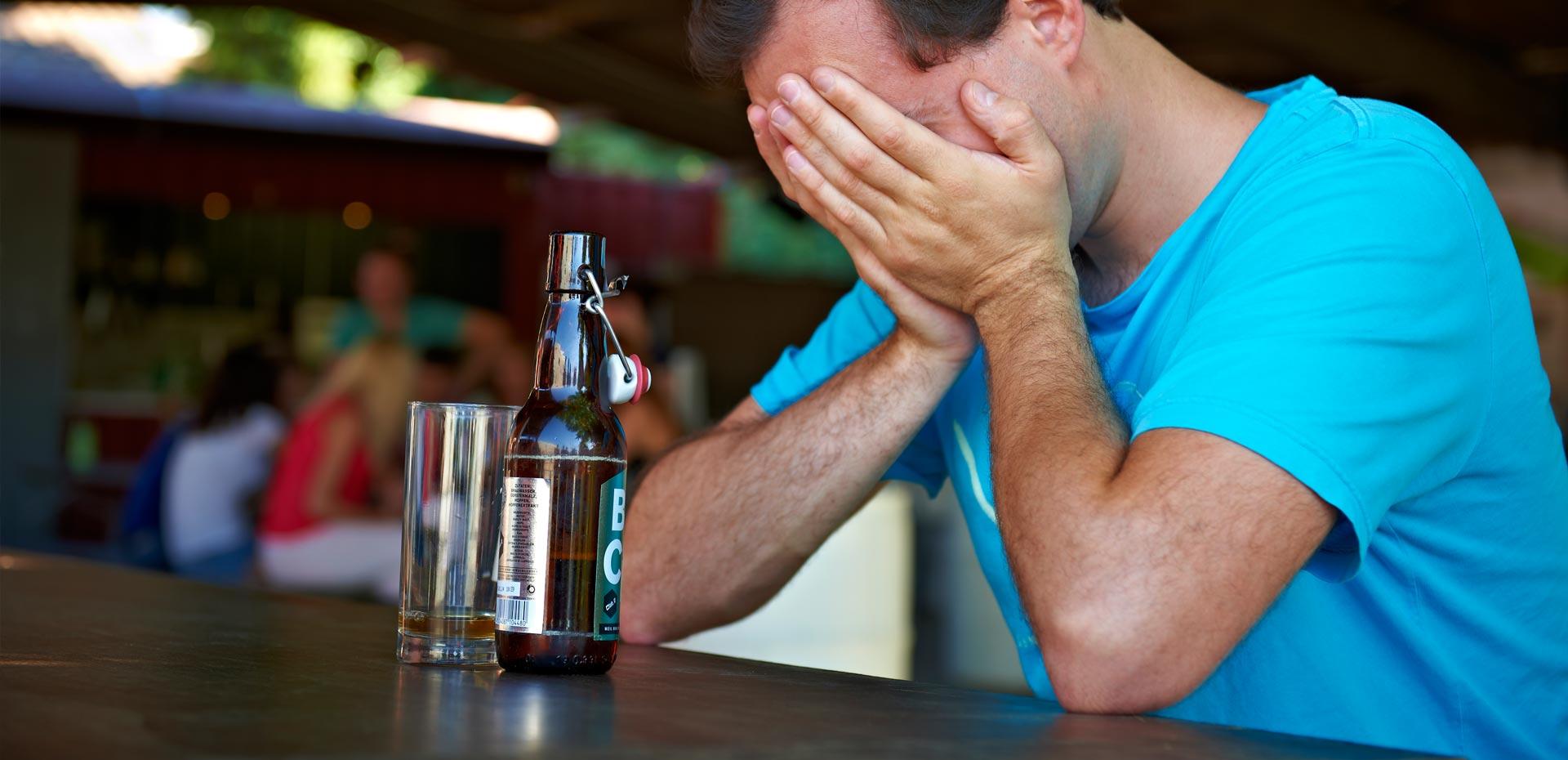 Verzweifelter junger Mann mit leerer Flasche