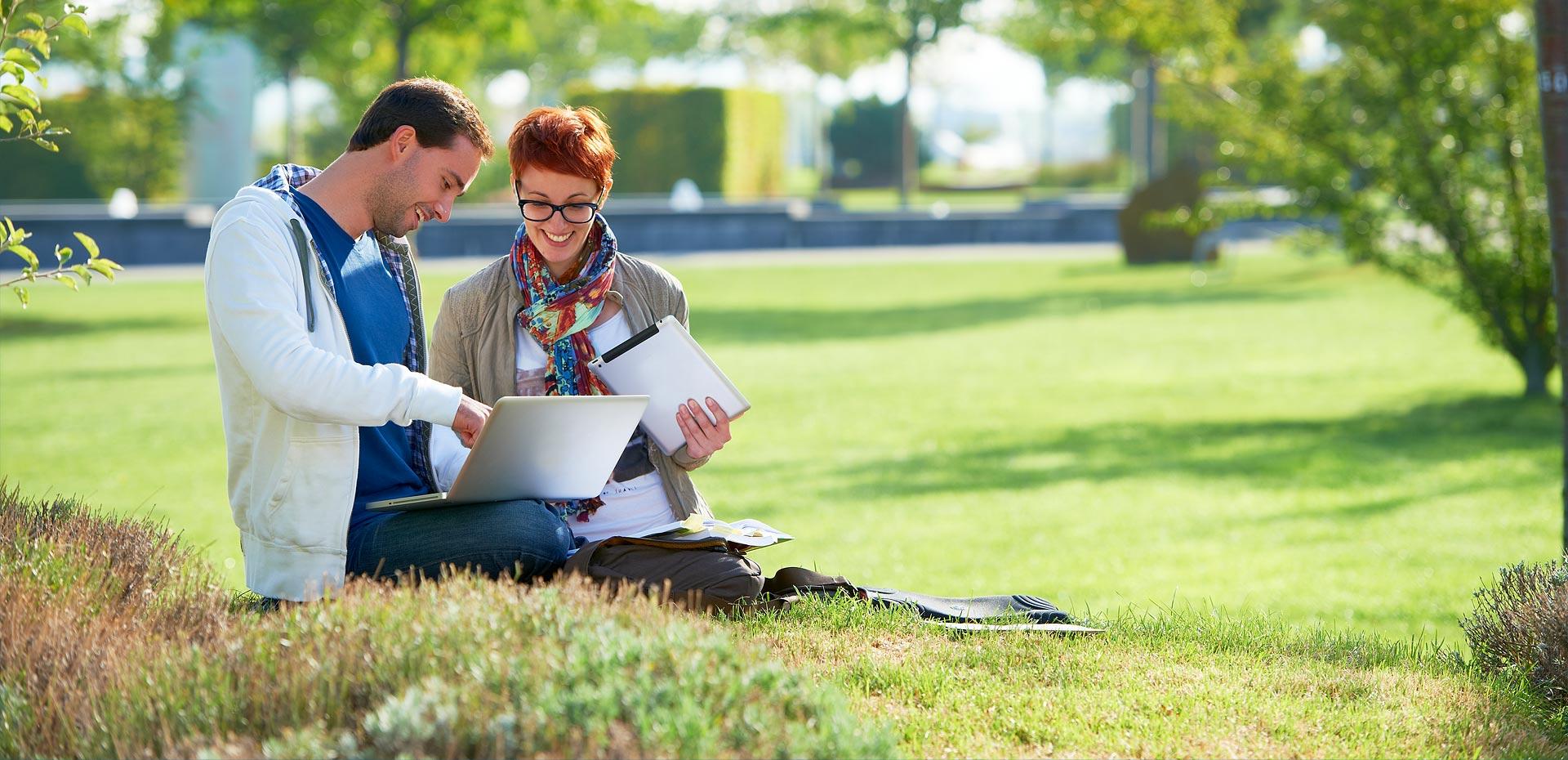 Ein junger Mann und eine junge Frau, die bei schönem Frühlingswetter draußen mit einem Laptop arbeiten