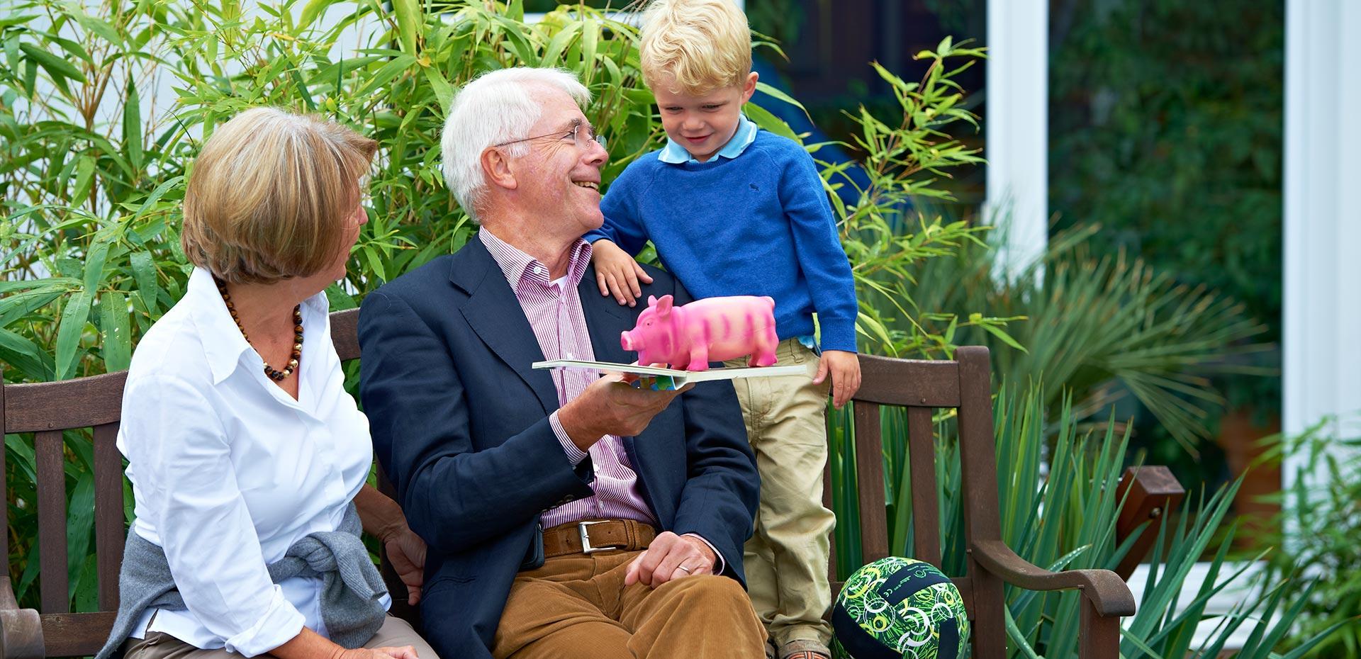 Opa und Enkel mit Bilderbuch und rosa Schweinchen