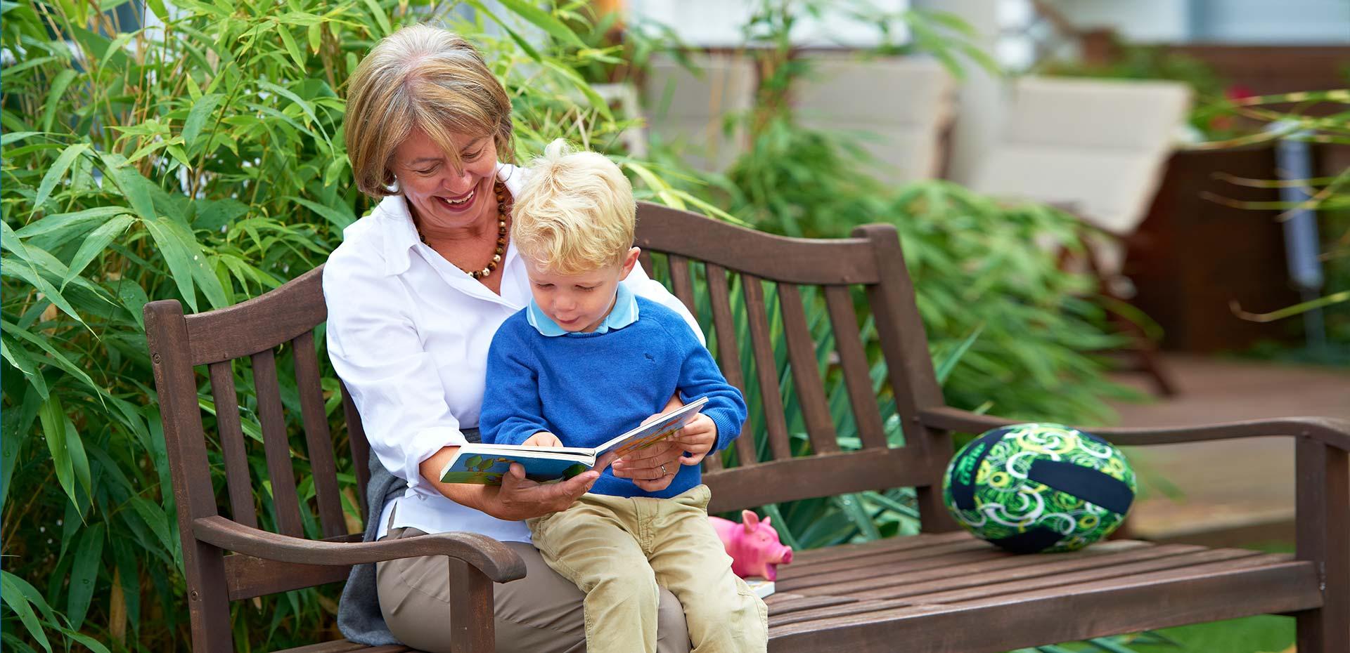 Oma und Enkel schauen sich auf einer Bank ein Bilderbuch an