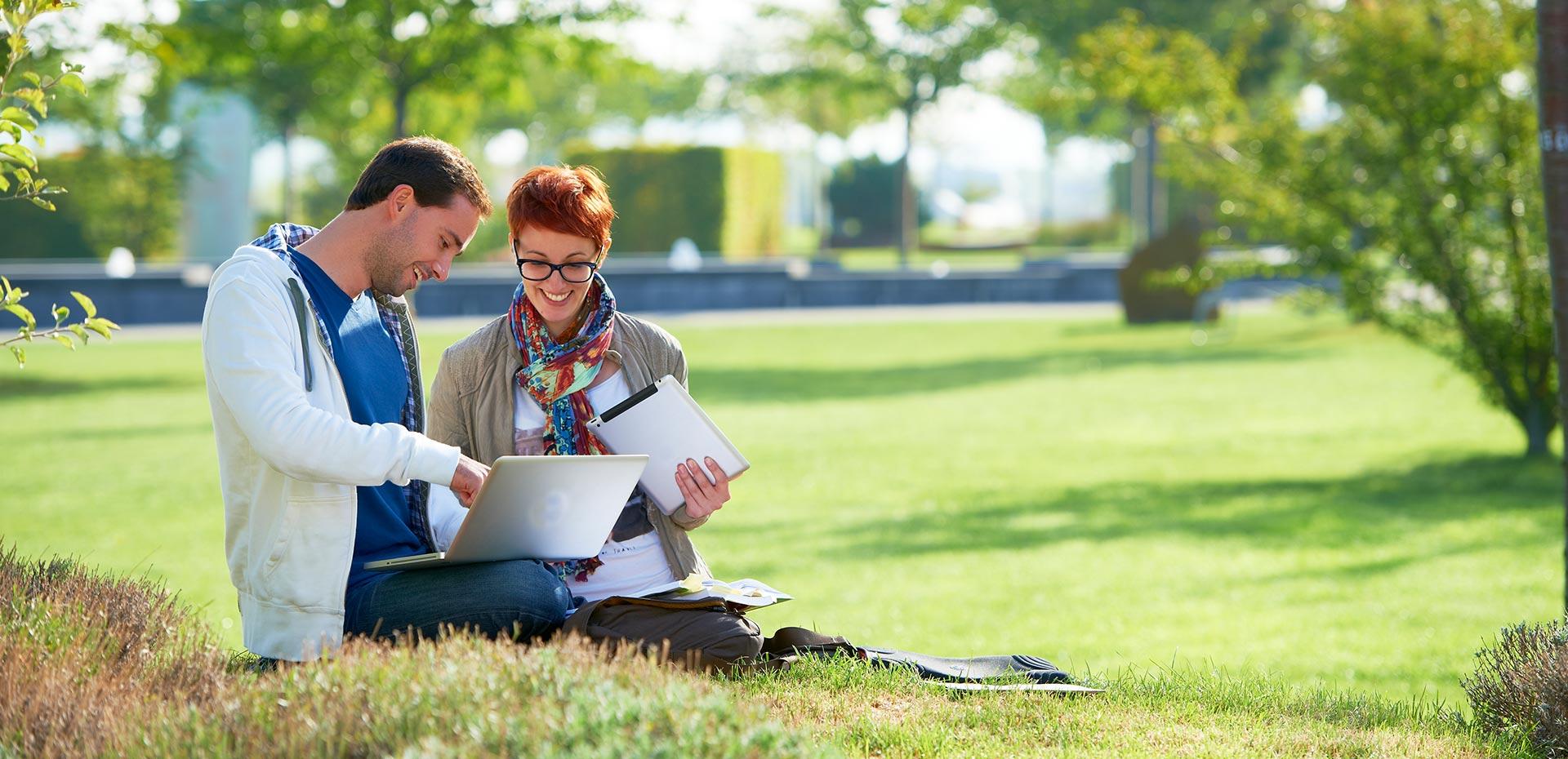 Junger Mann und junge Frau mit Laptop und Tablet