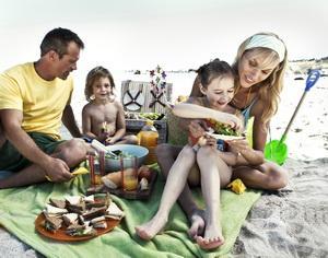 Junge Familie beim Picknick am Strand