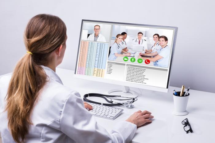 Ärztin in Videokonferenz mit anderen Ärzten
