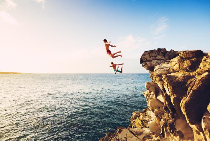 Zwei Männer springen von einer Klippe ins Meer