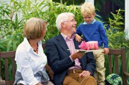 Oma, Opa und Enkel auf einer Bank mit einem Sparschwein