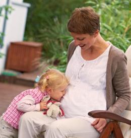 Tochter hört am Bauch ihrer schwangeren Mutter