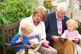 Opa und Oma mit Enkel und Enkelin auf einer Bank