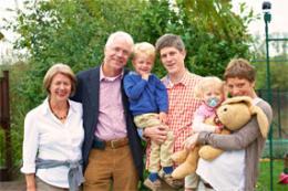 Familie im Garten mit Oma, Opa, Sohn, Vater, Tochter, Mutter und Hase
