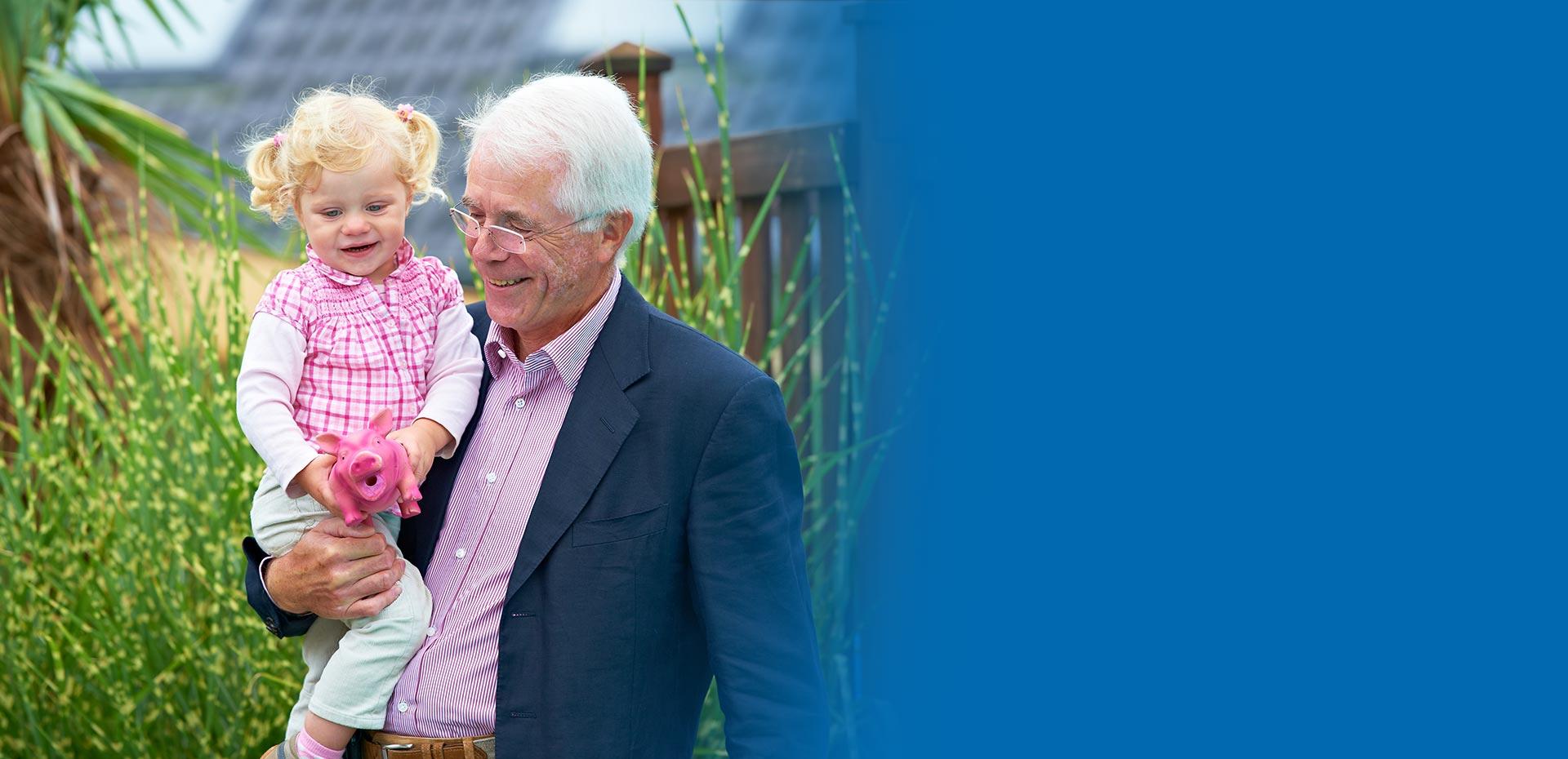 Opa hat Enkelin auf dem Arm, die ein rosa Schweinchen hält