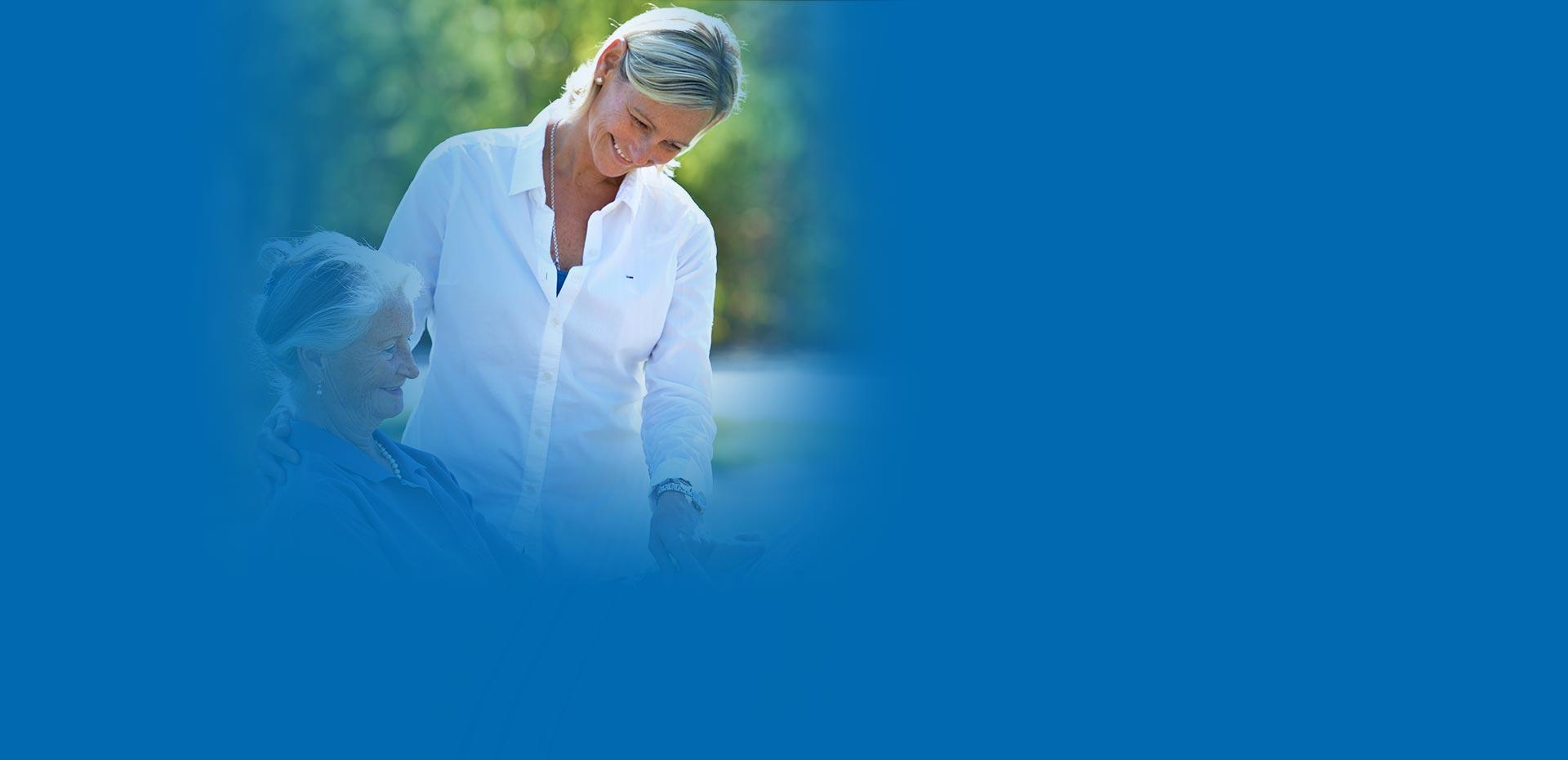 Sitzende ältere Frau und freundliche, stehende Pflegerin schauen zusammen eine Illustrierte an