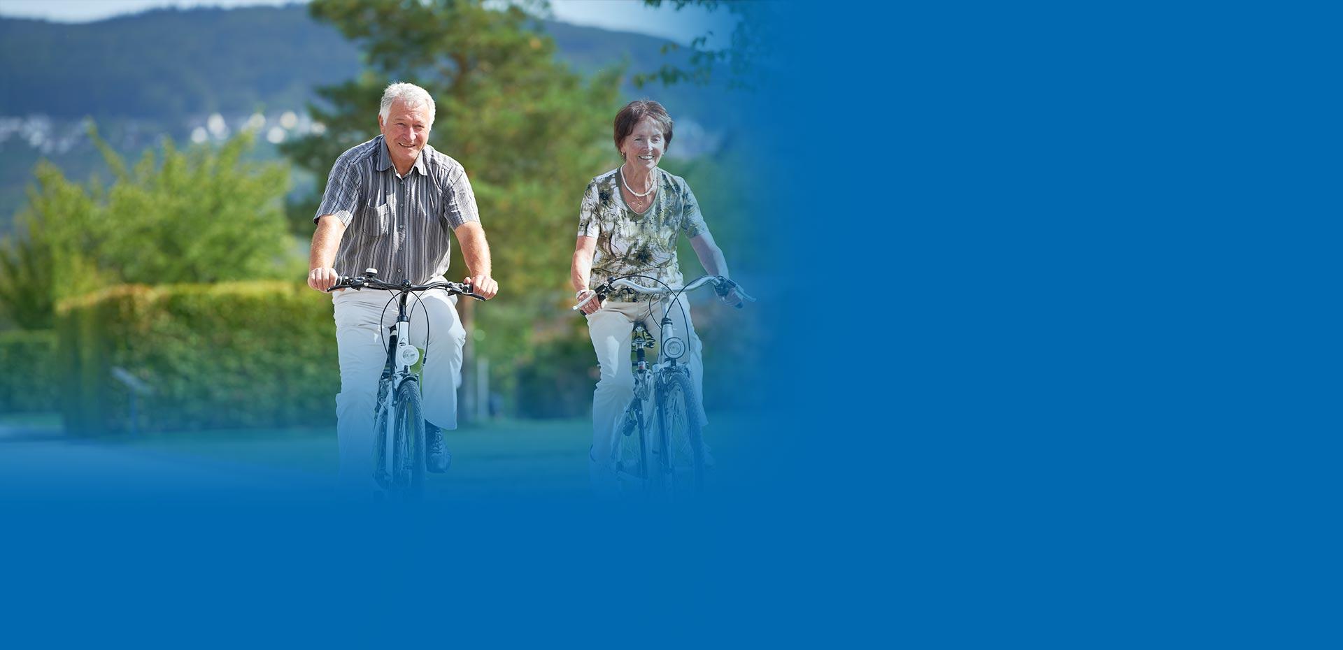 Ältere Frau und älterer Mann fahren vergnügt Fahrrad