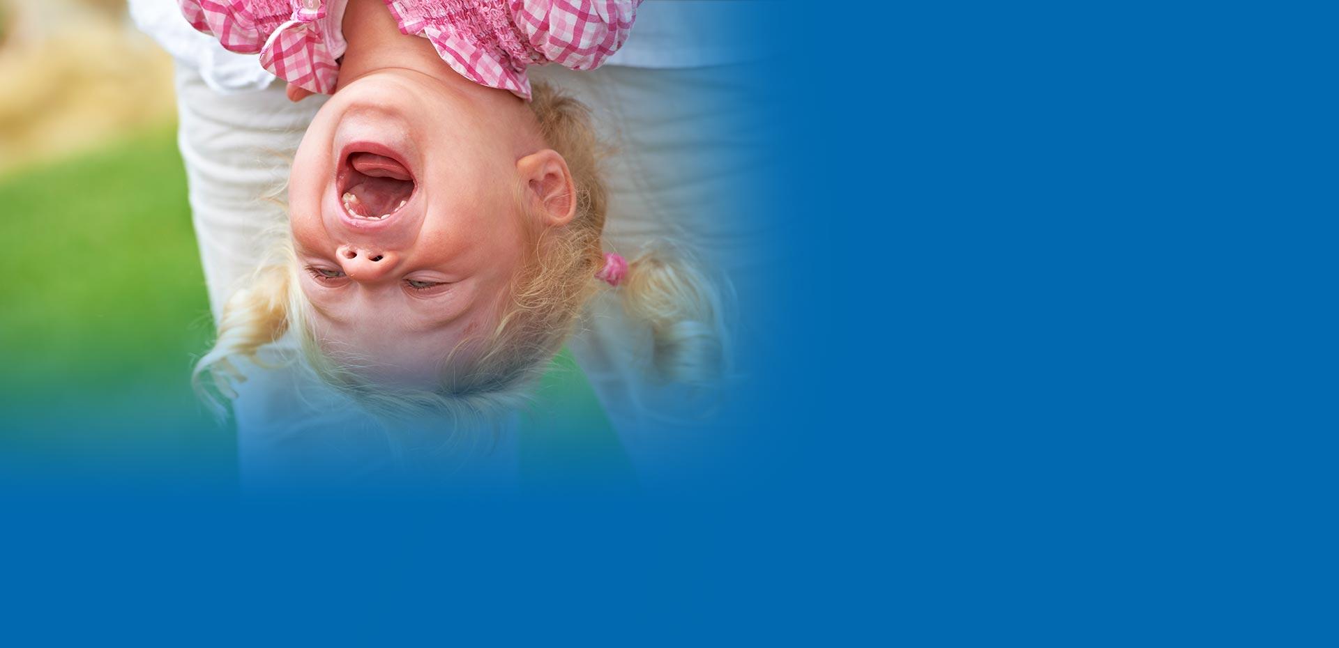 Mädchen hängt mit dem Kopf nach unten und lacht, so dass die Zähne sichtbar sind
